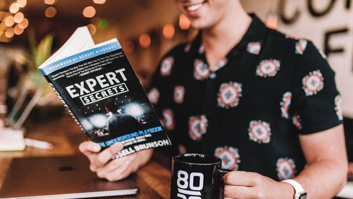 Eine junge Frau liest über die digitale Vermarktung in einem Buch, das von Experten geschrieben wurde