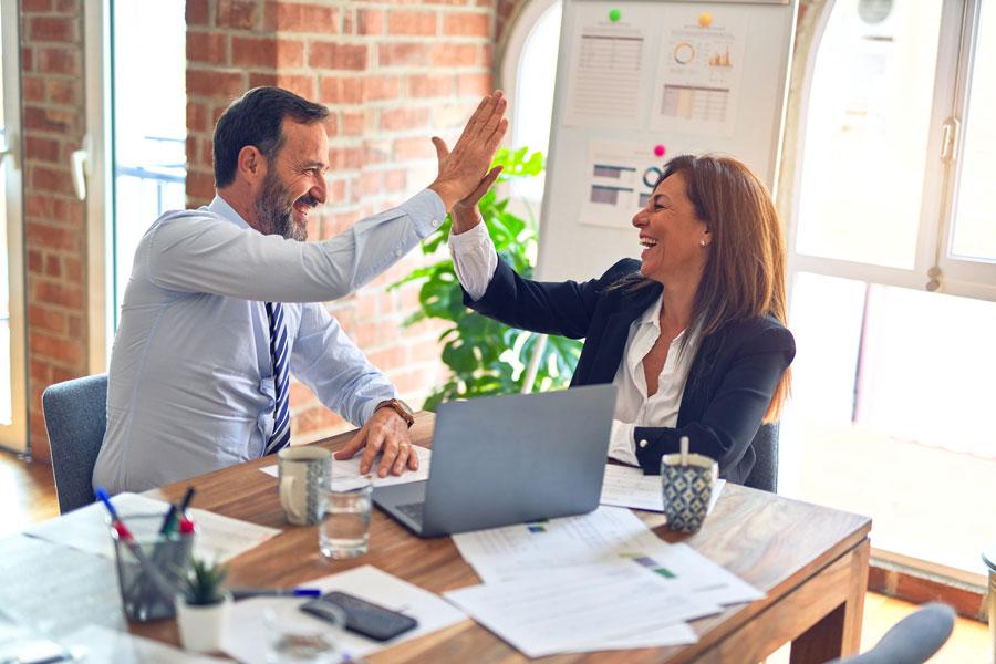 Eine Vertriebsberaterin feiert mit ihrem Kunden einen Vertriebserfolg