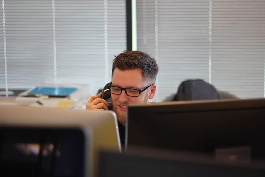 Ein Vertriebsmitarbeiter telefoniert und greift auf Daten vom Vertrieb zu, die zuvor digitalisiert wurden.