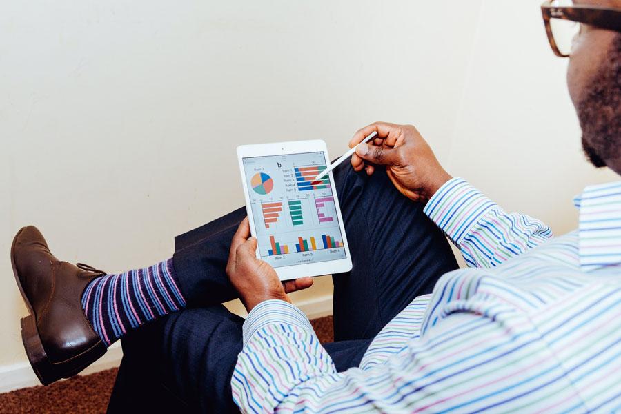 Ein Vertriebsberater zeigt eine Strategie auf dem Tablet auf
